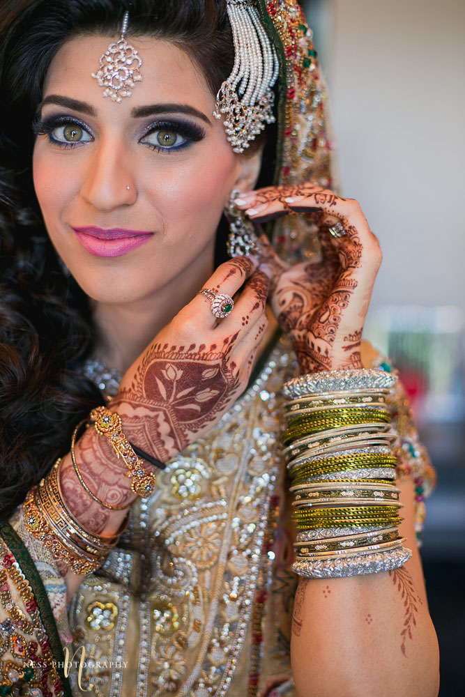 close up of pakistani bride makeup and her putting on her earrings at Shirley Wu beauty concept in toronto