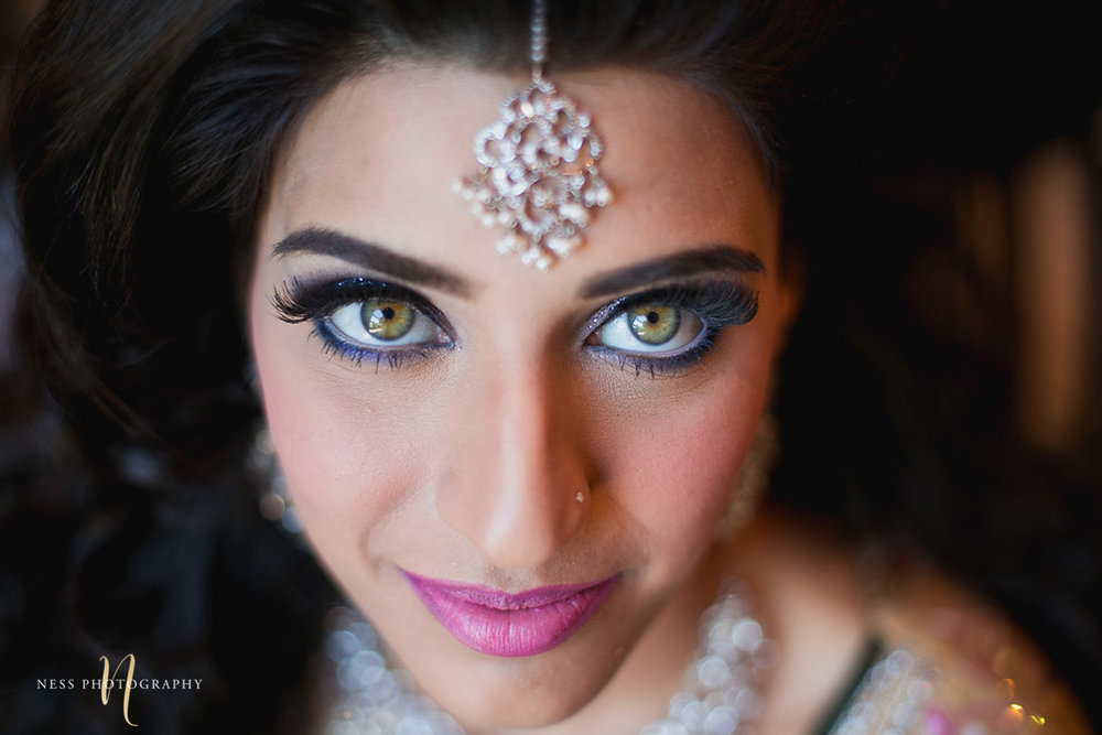 close up of pakistani bride makeup with green eyes and tikka