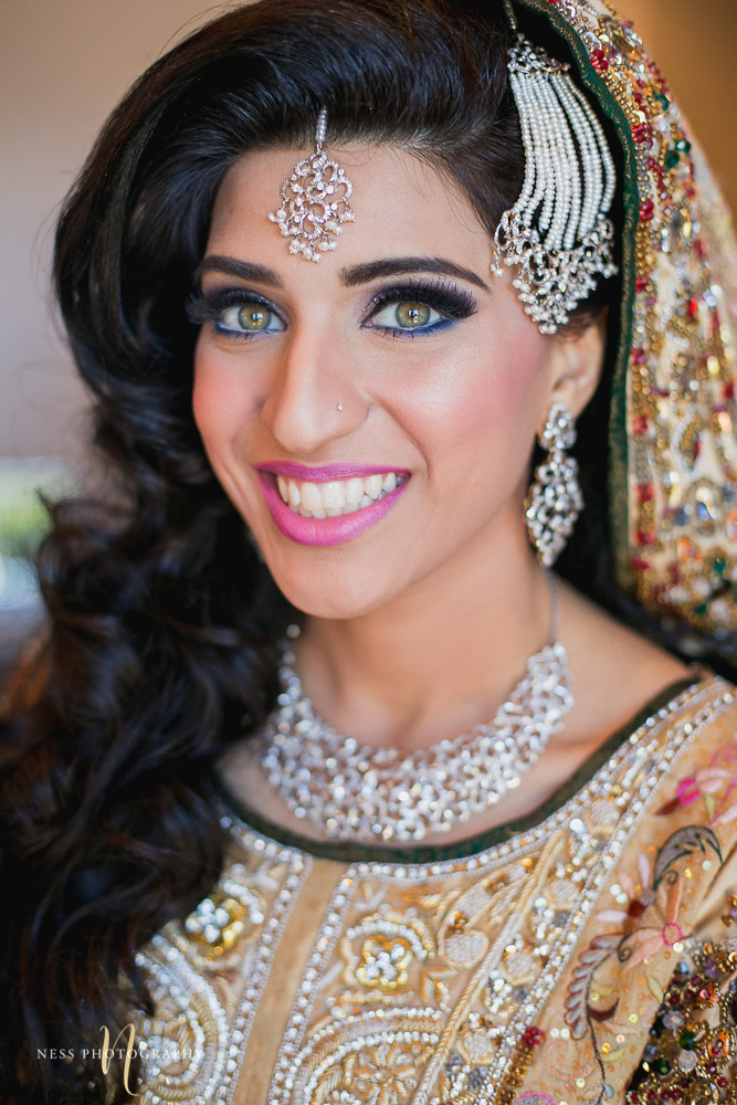 pakistani bride with green eyesl ooking at the camera and smiling wearing tikka and jhumar passa