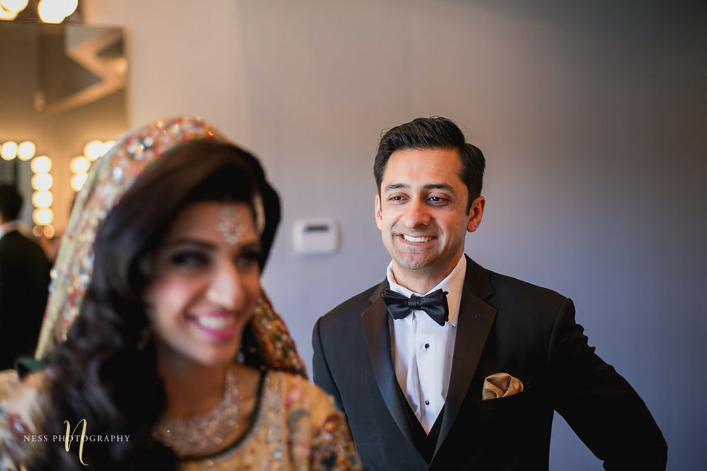 groom in tux walks towards the bride as she is getting ready for the first look at her pakistani wedding in toronto