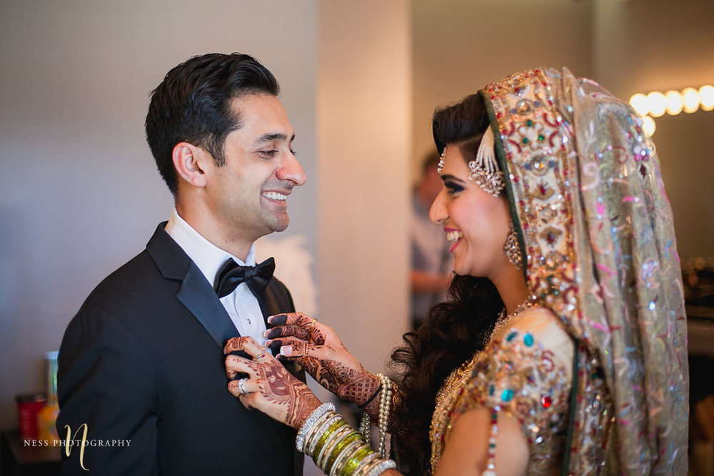 pakistani bride and groom turn towards each other and smile for the first look at Shirley Wu beauty concept in toronto