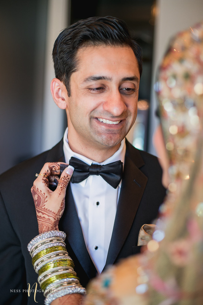 pakistani bride smiles at the groom after the first look and fixes his bow tie