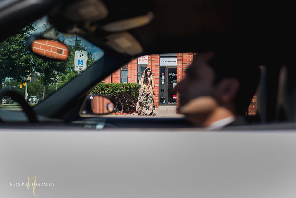 groom sitting in the car outside Shirley Wu beauty concept in toronto and the bride walking towards him,
