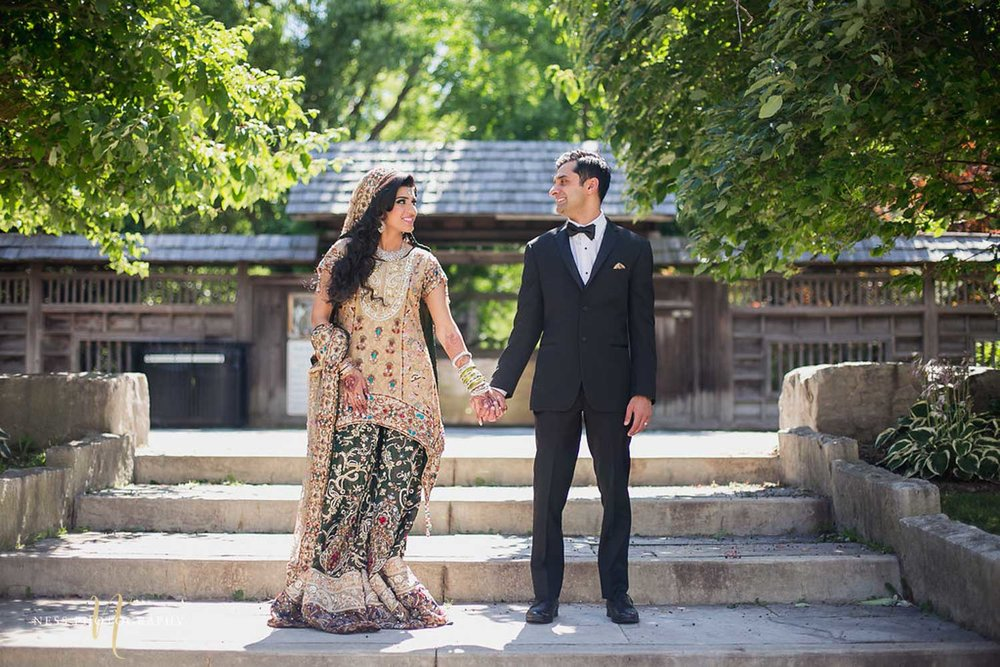 Pakistani bride in green lehenga holding hands with groom in black tux outside kariya park in mississauga  , Toronto