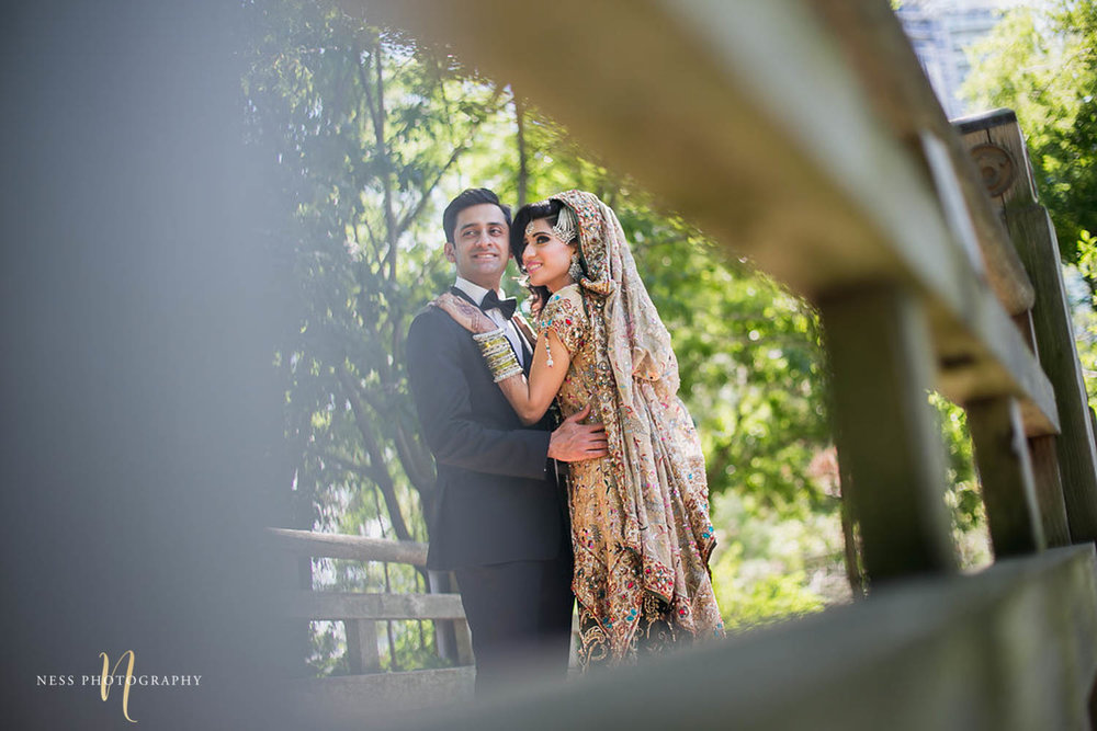 a bridal photo of pakistani bride and groom hugging with the bridge blurry in the foreground