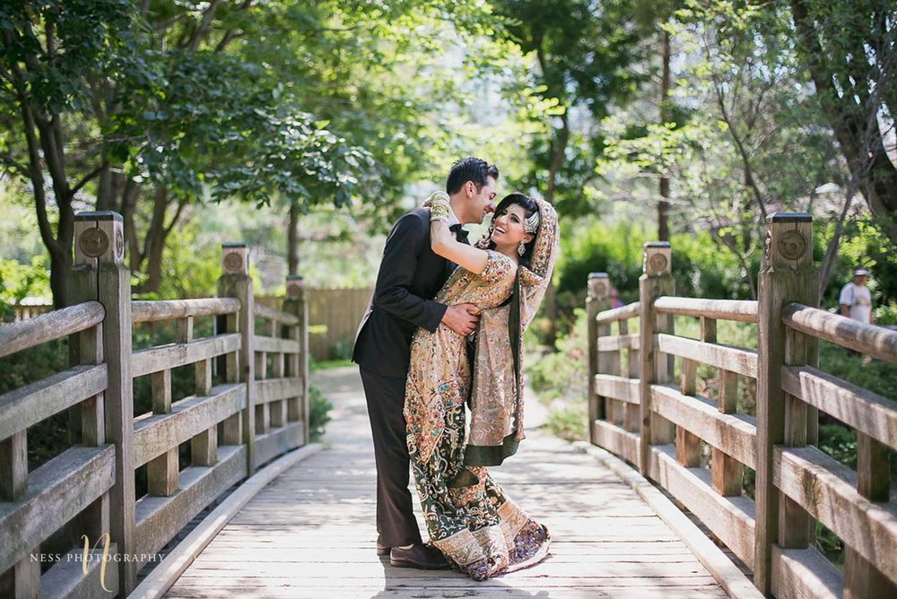 pakistani bride in black tux and bride in green lehenga holding each other and laughing on the bridge at kariya park in mississauga
