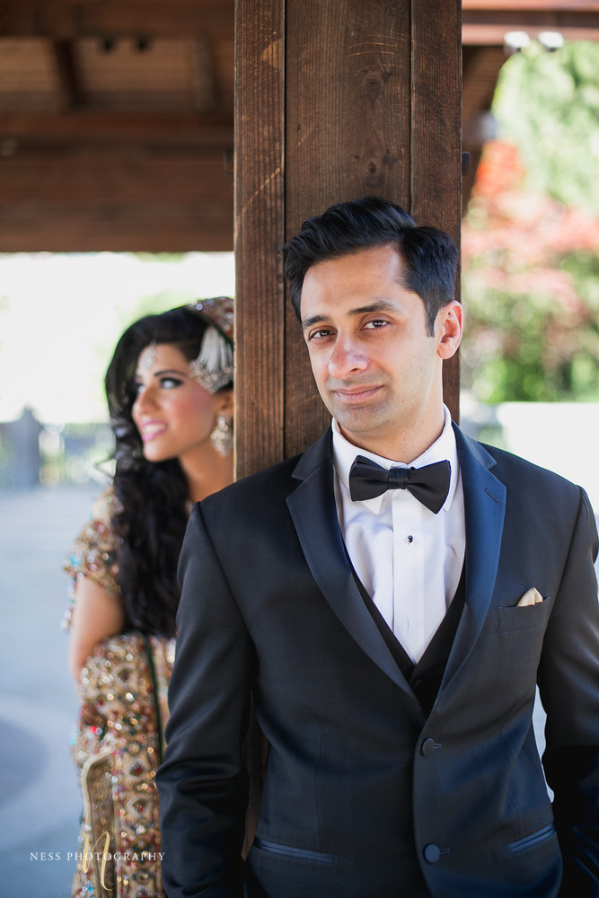groom standing against wooden wall pole with pakistani bride in lehenga clurry in the background at kariya park
