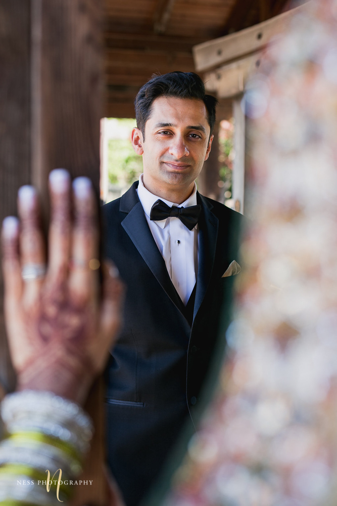 pakistani groom in black tux looking at his bride and her in the front blurry at kariya park