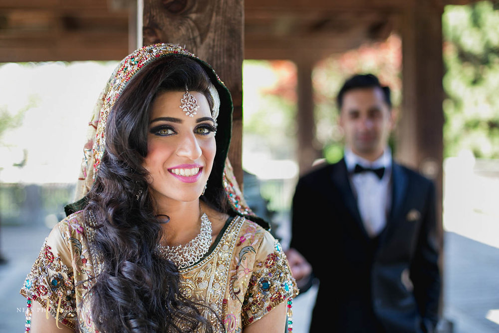 pakistani bride in green lehenga and tikka looking at the camera and groom in black tux blurry in the background at kariya park