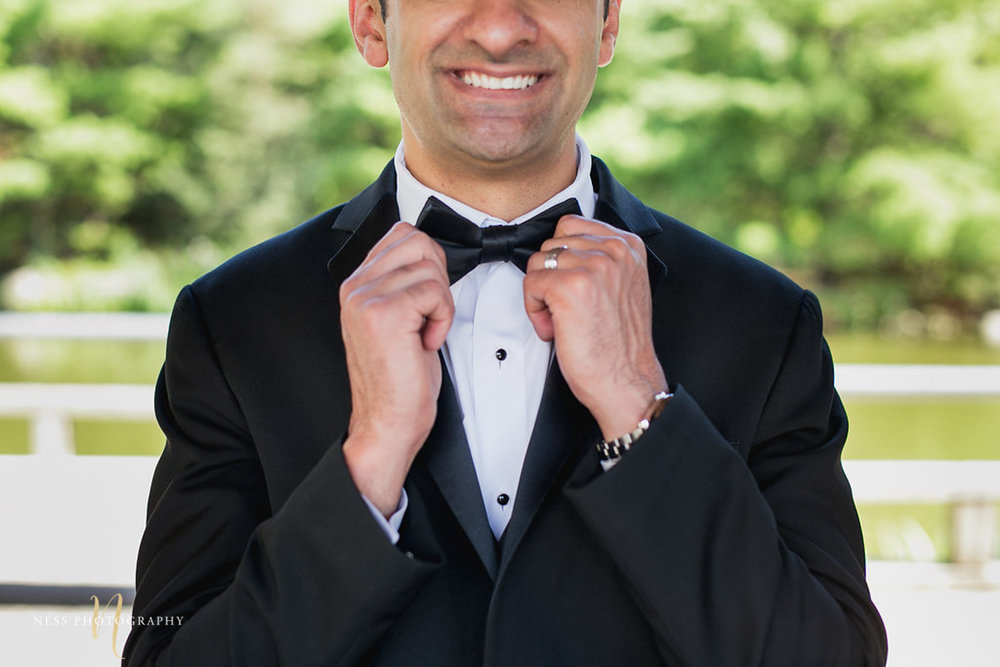 bridal photo of pakistani groom at kariya park fixing his bow tie