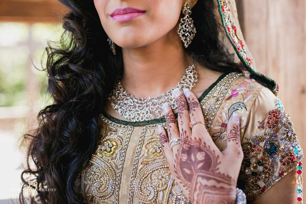 pakistani bride with pink lipstick touching her necklace with mehendi on her hands at kariya park