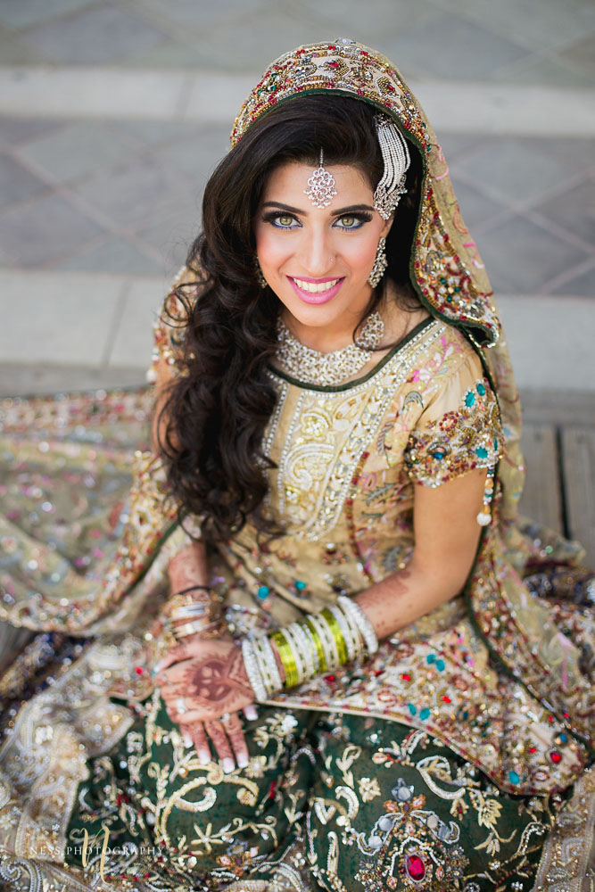 pakistani bride with green eyes sitting on the ground at kariya park and looking straight at the camera wearing green lehenga