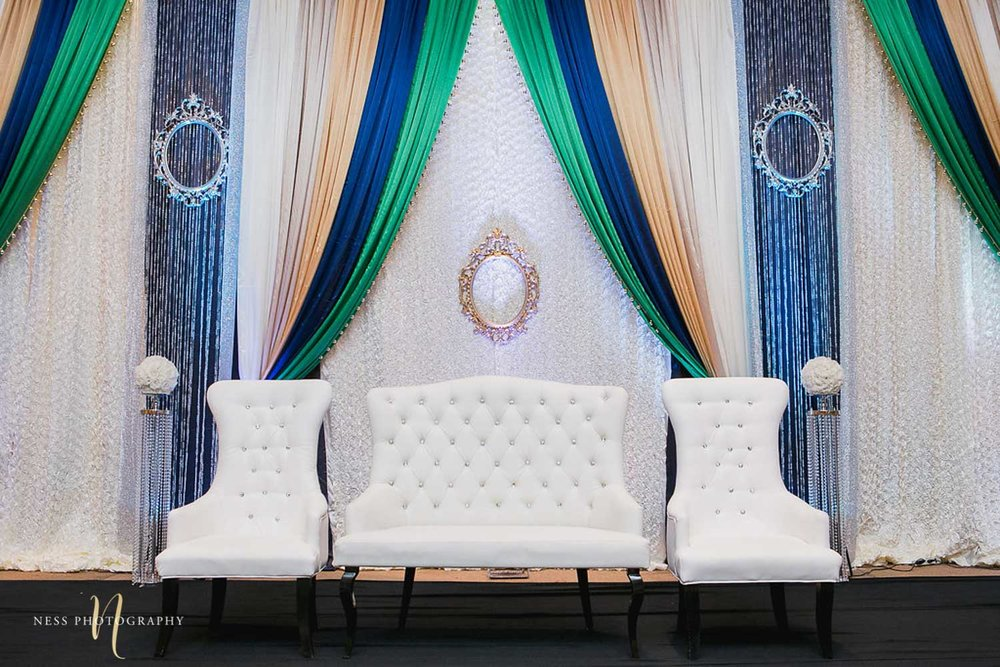 white couch on  stage steup with green and bleu background for pakistani wedding walima at payal banquet hall in mississauga