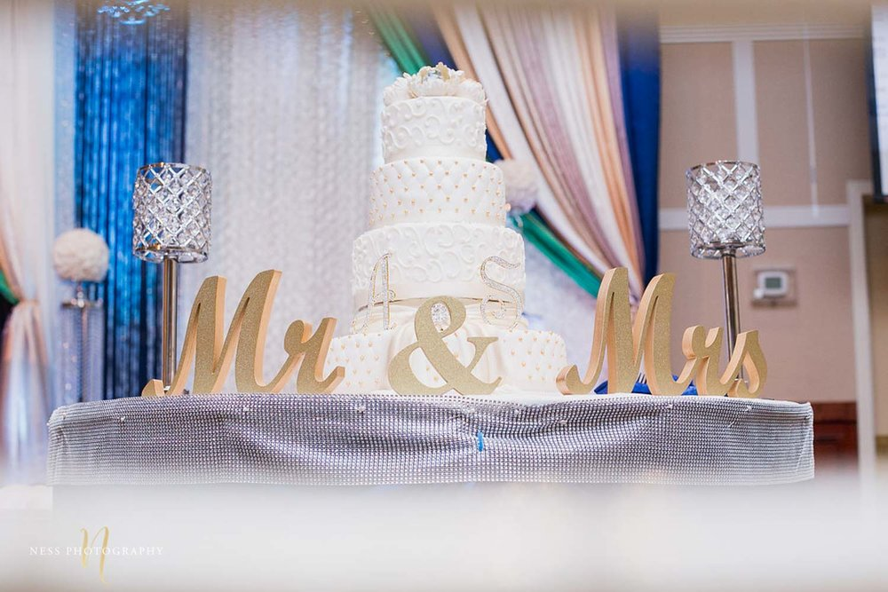white lace cake with mr and mrs sign in front at walima in payal banquet hall