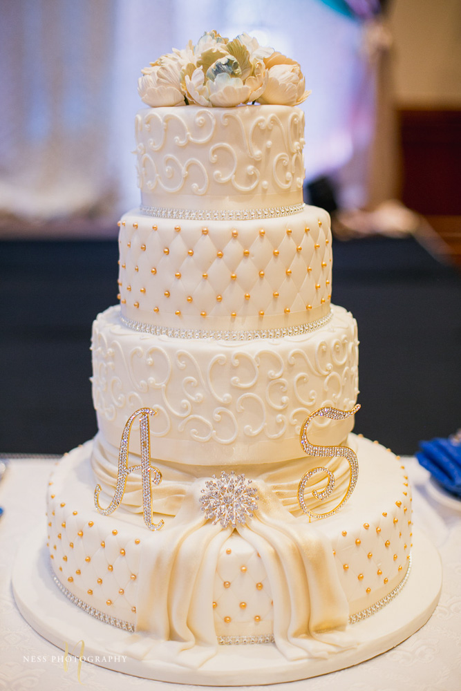 closeup of white lace cake with blurry background at walima reception payal hall