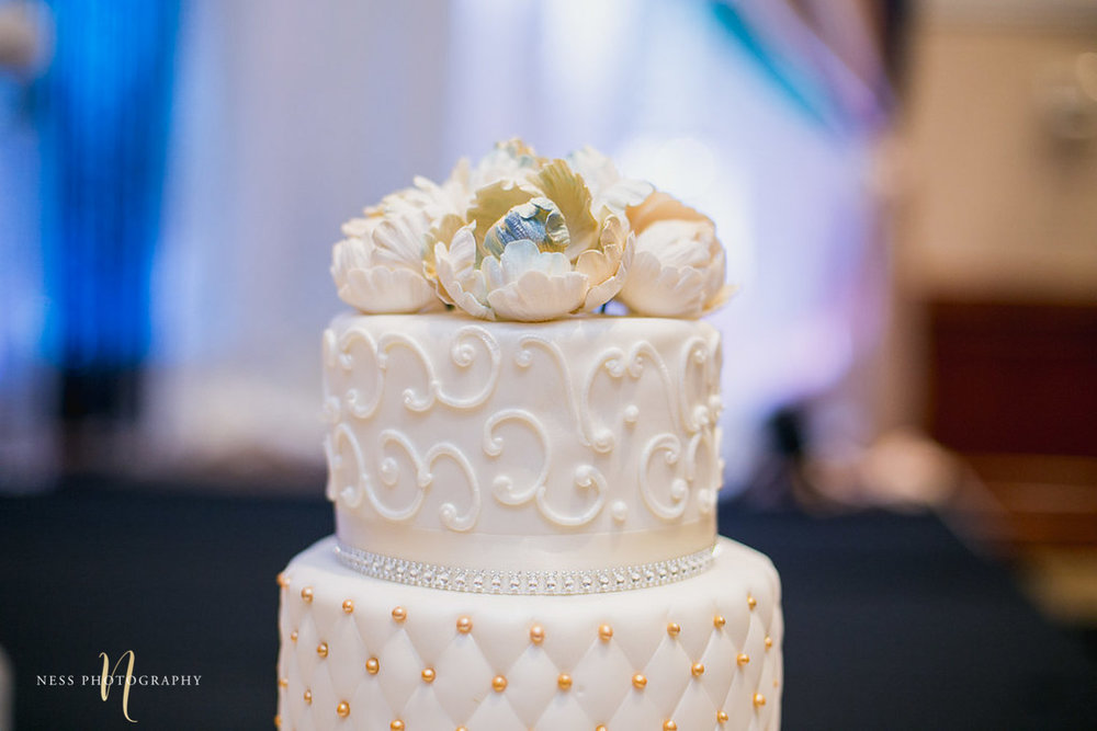 closeup of white floral cake topper at walima reception at payal banquet hall