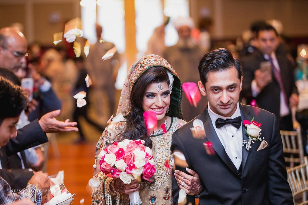 guests throw rose petals as the bride and groom holding hands enter payal banquet hall for their pakistani walima reception