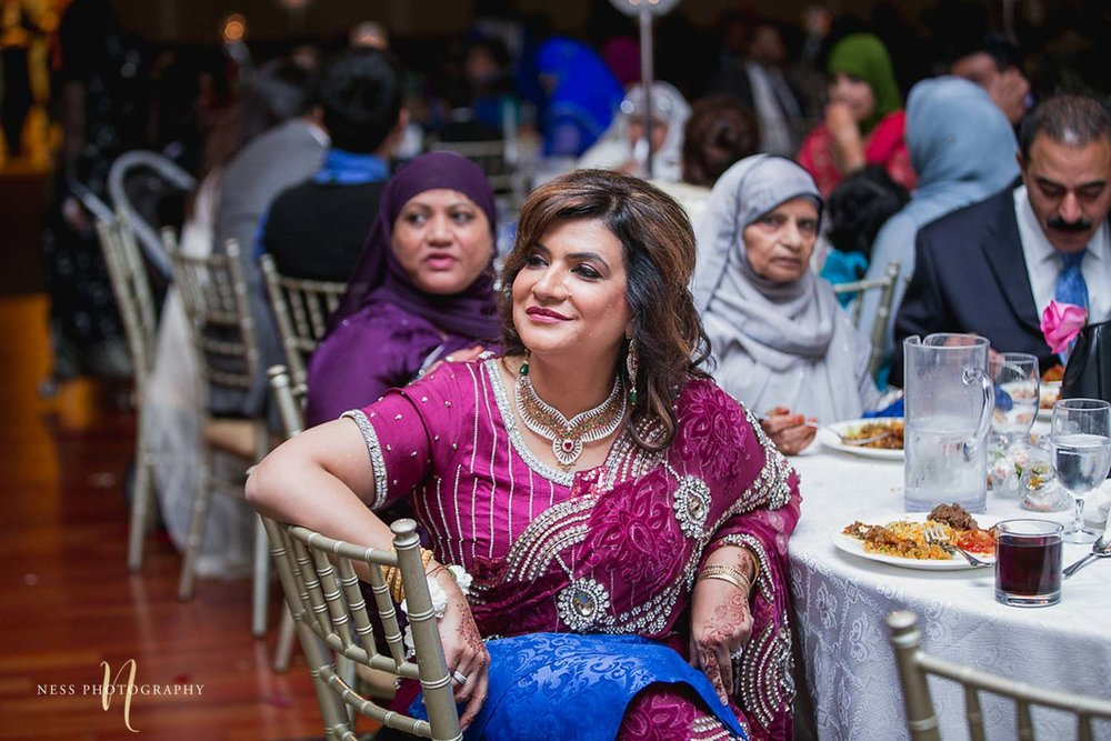 mother of the bride in purple lehenga watching the walima reception speeches