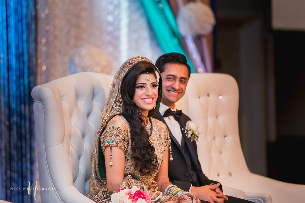 pakistani bride and groom sitting on white couch on the walima stage and laughing at the speeches