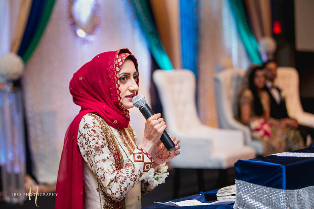 sister of the groom wearing red hijab and holding microphone during pakistani walima reception at payal hall