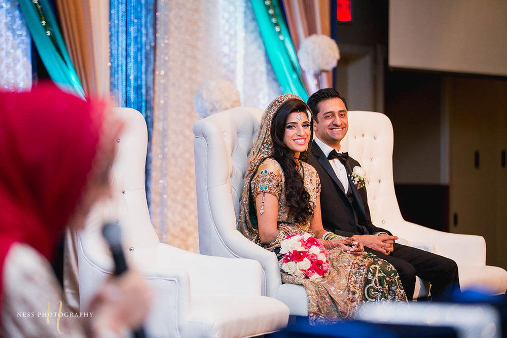 bride and groom laughing and looking at the sister giving a speech during pakistani walima reception