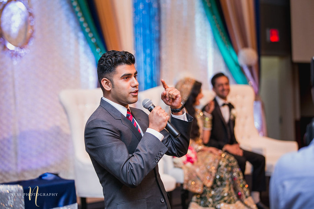 brother of the groom in grey tux giving a speech and the groom and bride laughing in the back ground at walima reception