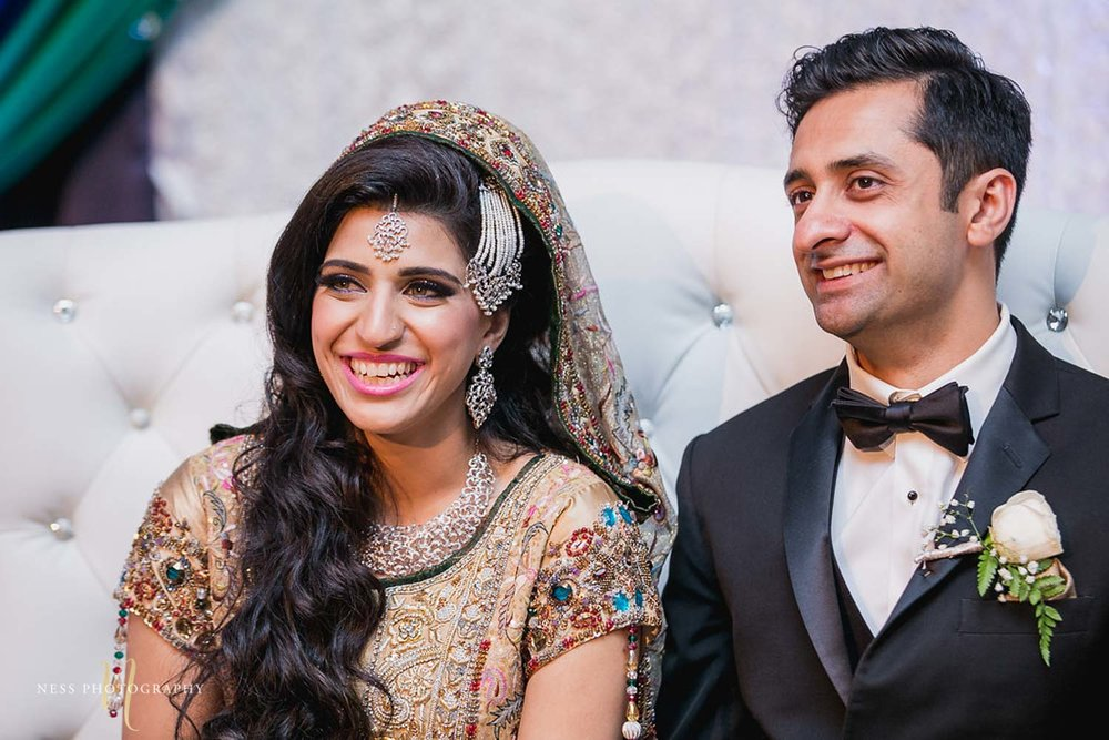 closeup and bride and groom sitting next to each other and laughing at walima reception