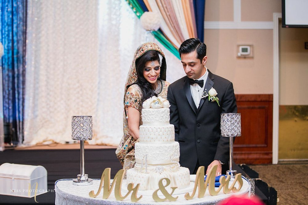 bride in green lehenga and groom in black tux cutting a white lace cake during walima reception