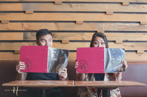 couple hiding their faces behind the menu at Cacao 70 Engagement shoot Montreal