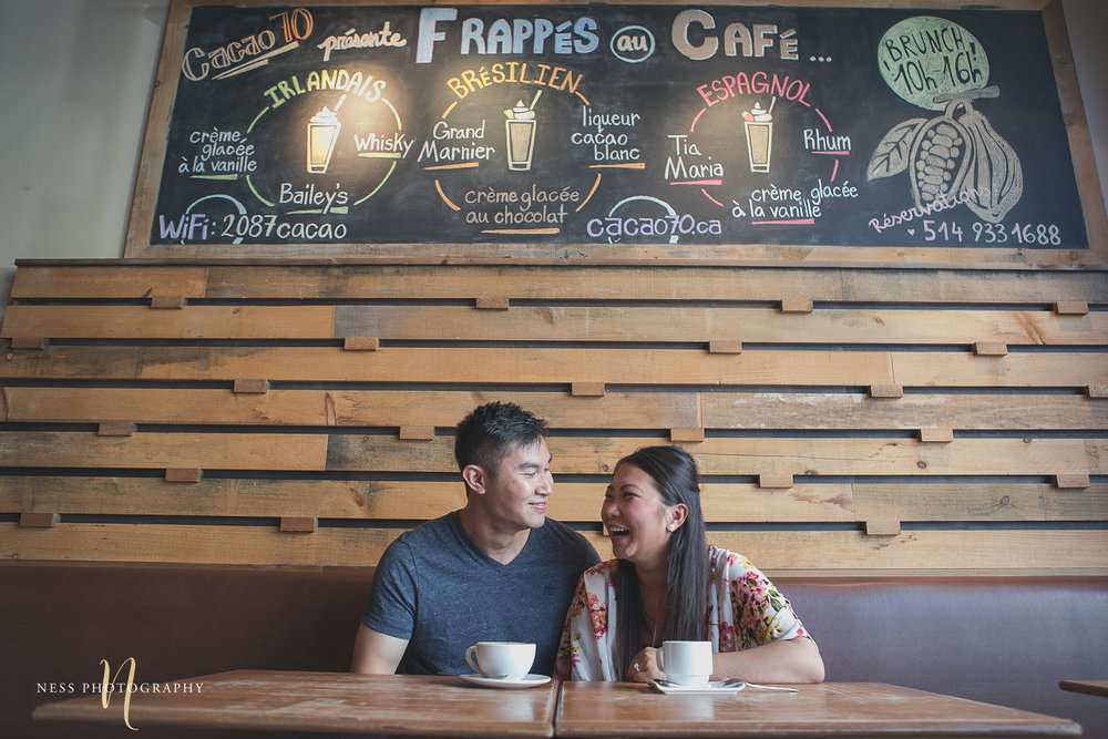 couple sitting on the table and laughing and Cacao70 chalk board menu in the background Engagement shoot Montreal