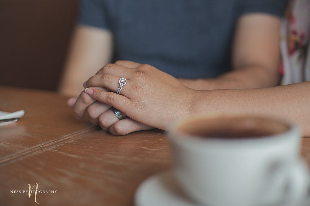 coffee cup in the front and couple holding hands in the back with ring during Cacao 70 engagement shoot Montreal