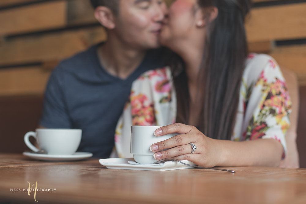 couple kissing in the background and girl holding coffee cup at cacao70 engagement photo session in montreal