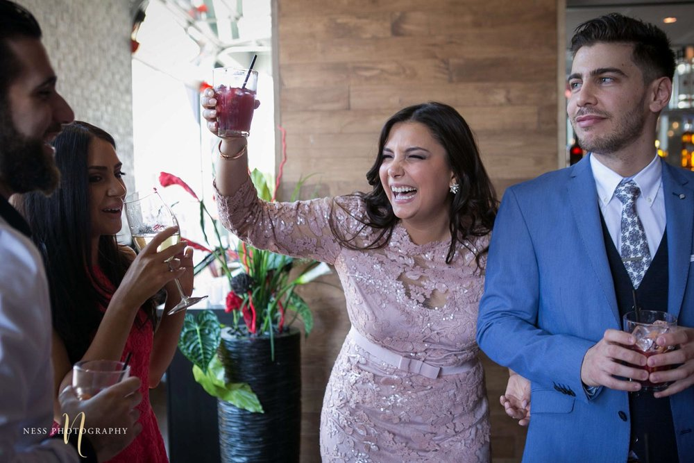 bride to be in pink dress toasting with guests at engagement Party in Montreal