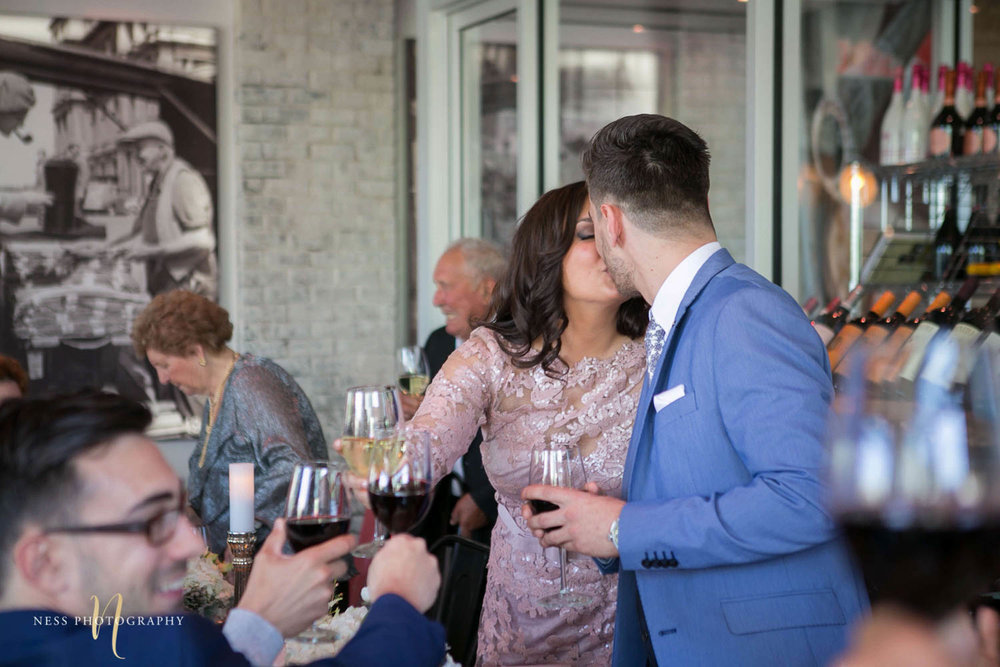 bride and groom to be kissing after speech at engagement Party in Montreal