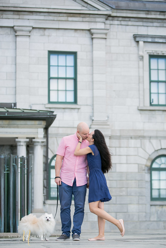 couple at engagement photoshoot walking white dog in the old port of montreal