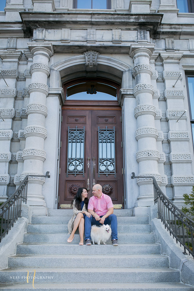 coupld sitting in front of old french building in the old port of montreal for engagement photoshoot with their dog