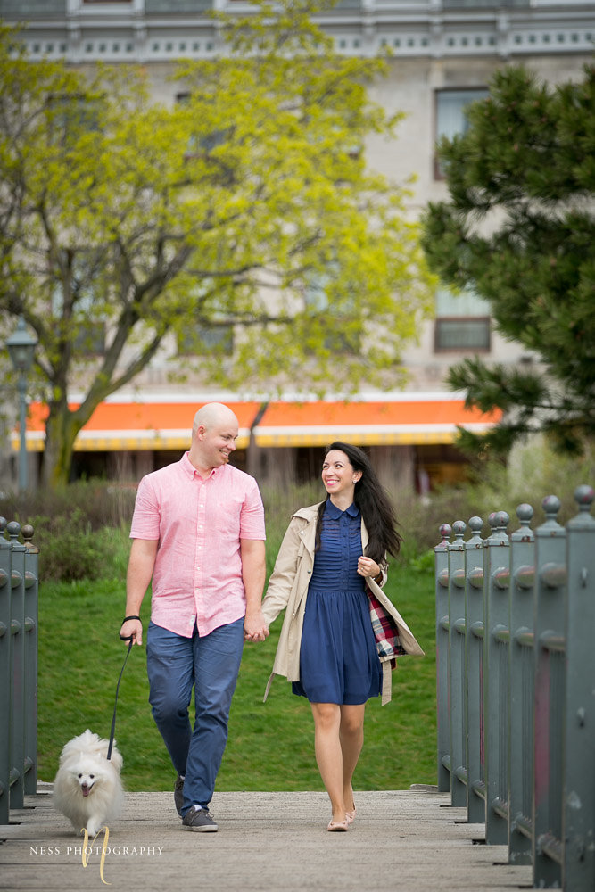 couple walking their dog on a bridge in the old port of montreal during their engagement photos