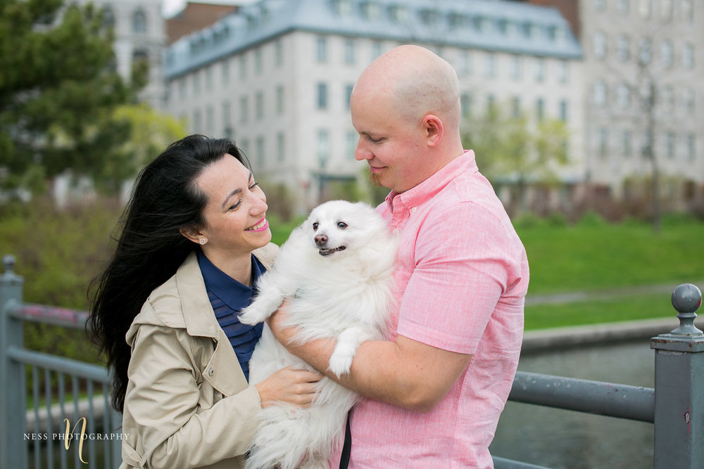 couple holding their white dog and laughing during engagement photoshoot