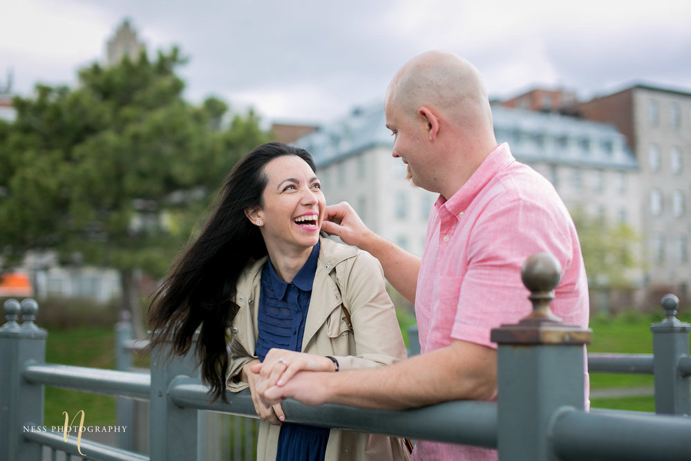 Couple looking at each other and laughing on a bride in the old port of montreal during their engagement photoshoot