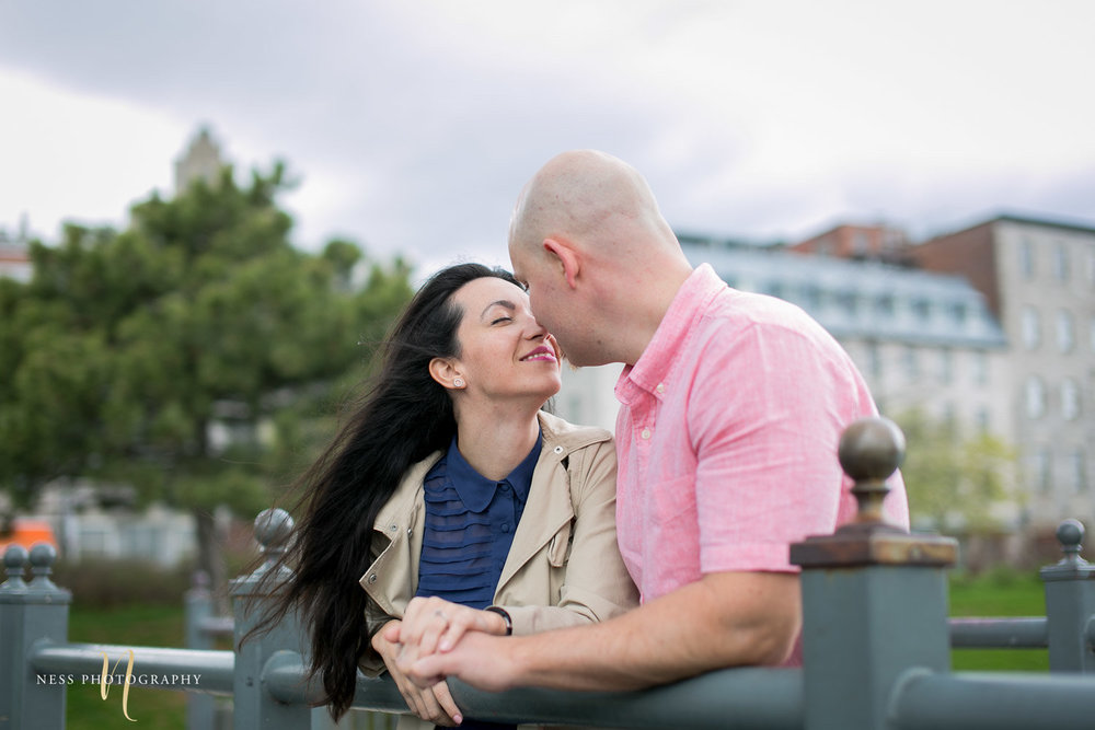 couple kissing on top of bridge in old port of montreal during their pre wedding engagement photos