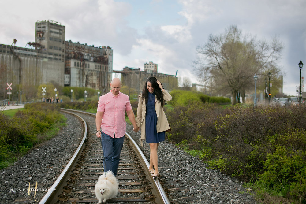 couple walking with their dog on train rails in the old port of montreal during engagement photo shoot