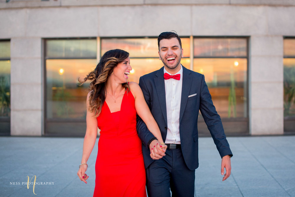couple holding hands and laughing in front of Montreal Saint joseph Oratory during sunset engagement session