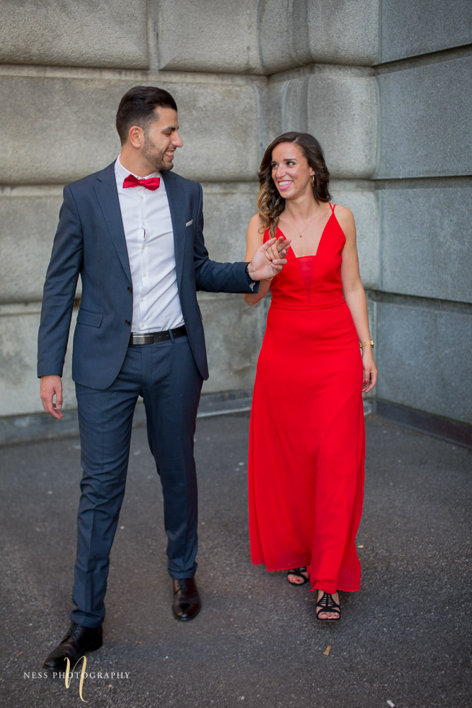 couple in red dress and bleu suit holding hands and walking in montreal saint joseph oratory during sunset engagement session