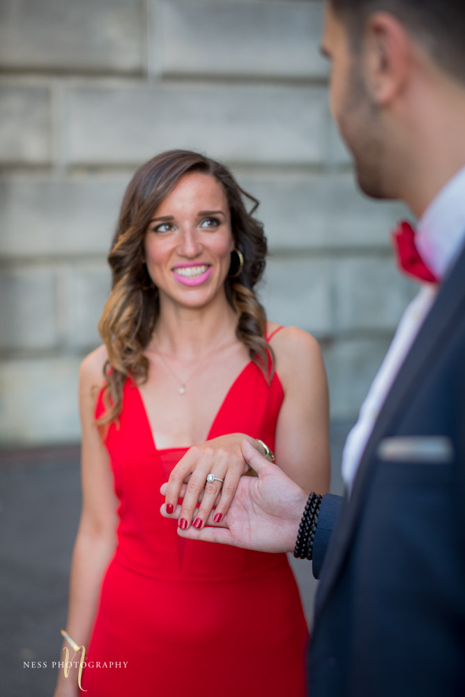 couple in red dress and bleu suit holding hands and closup on the ring at montreal saint joseph oratory during engagement session