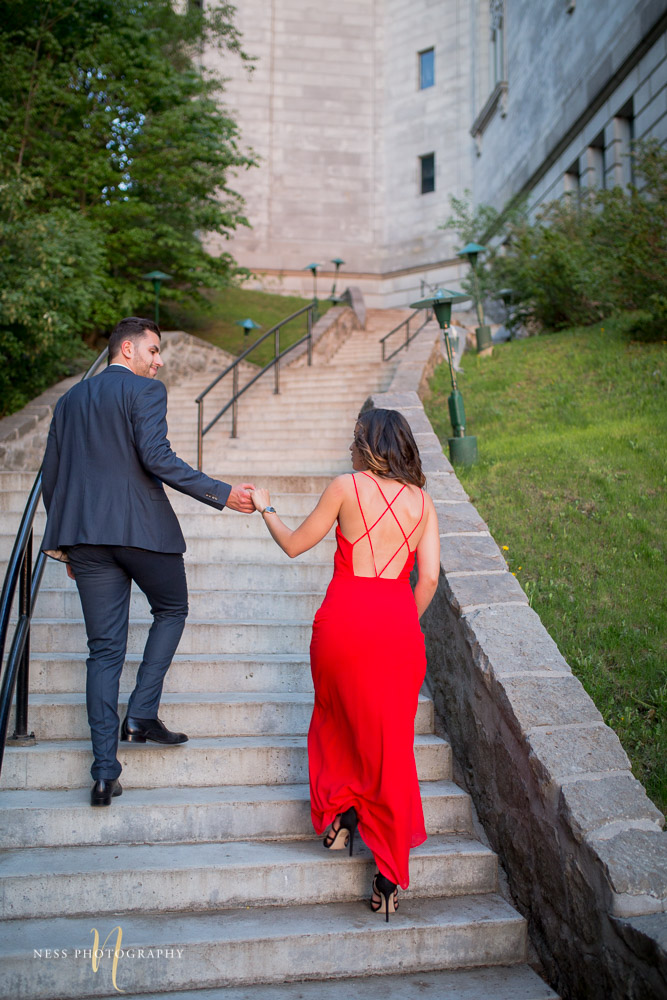couple in red dress andb leu suit going up the stairs at oratoire saint joseph during engagement photoshoot