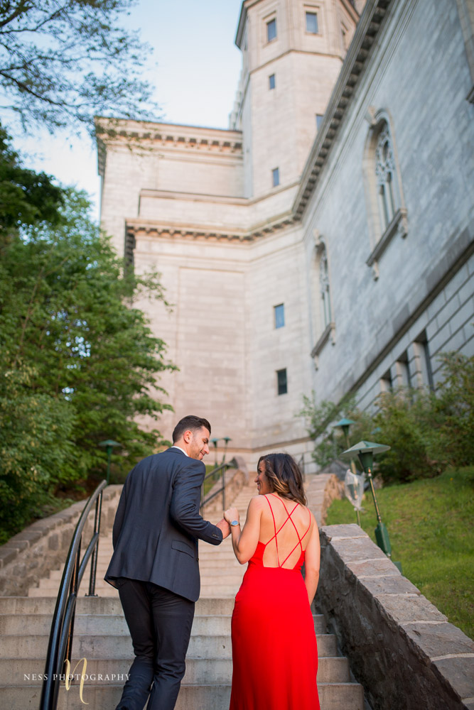 couple in red dress andb leu suit going up the stairs at montreal oratoire saint joseph during engagement photoshoot