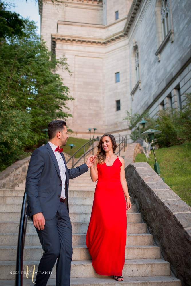 couple in red dress and bleu suit going down the stairs at montreal saint joseph oratory during engagement session