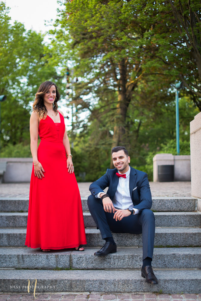 groom sitting on stairs and bride in red dress during formal engagement session at montreal saint joseph oratory