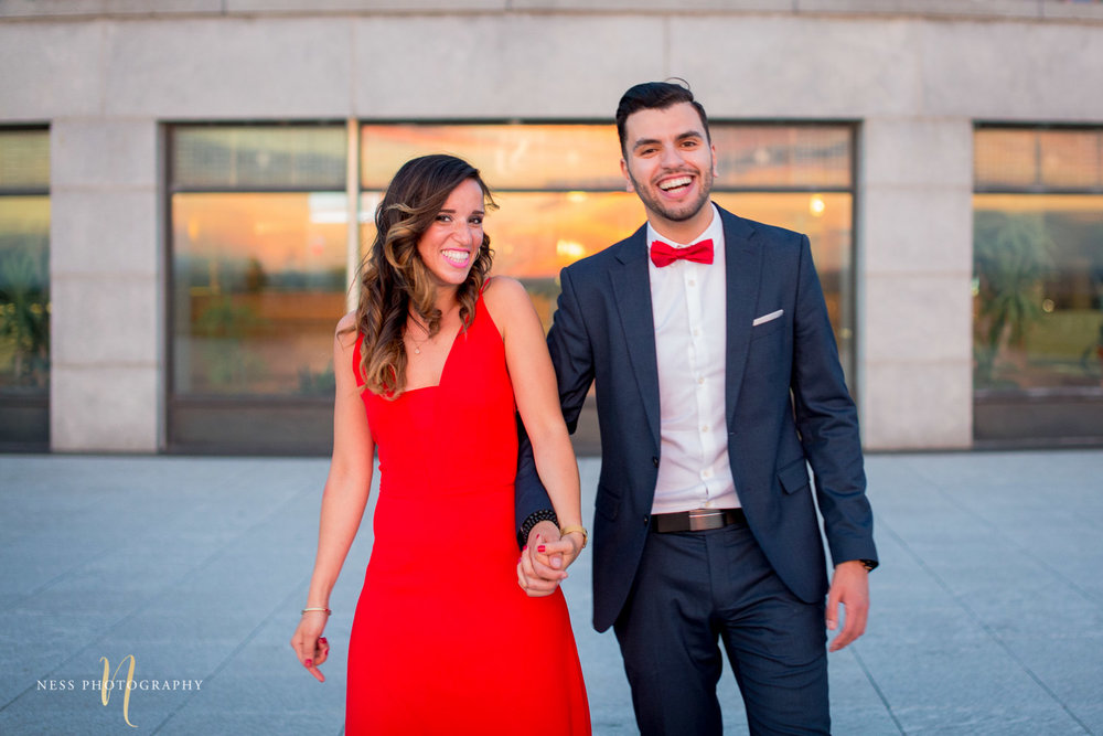 couple holding hands and laughing during montreal engagement session at oratoire saint joseph