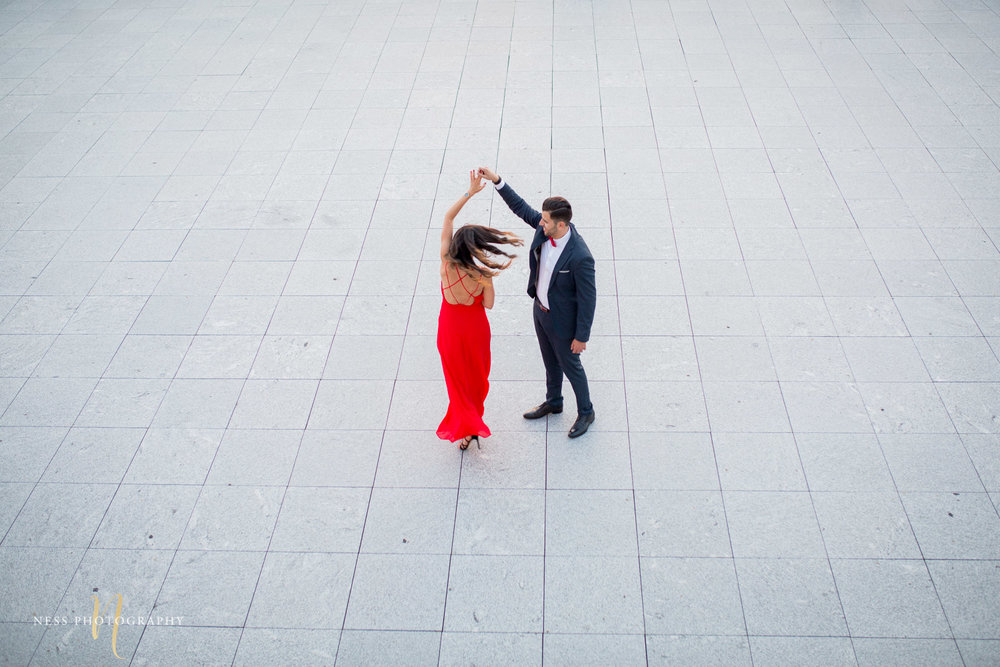top down view of couple dancing during elegant engagement session in red dress with montreal wedding photograher